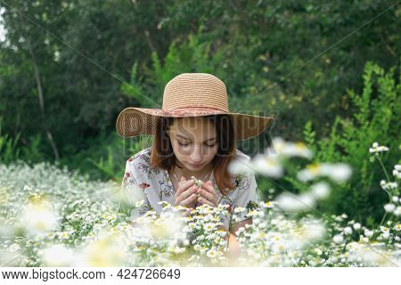 Beautiful Girl Sniffs Daisies In Nature. Girl In A Hat On A Flower Field. Gentle Portrait Of A Girl