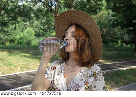 A Young Girl Drinks Water From A Bottle In Nature. Pure Drinking Water In A Plastic Bottle. Quenchin