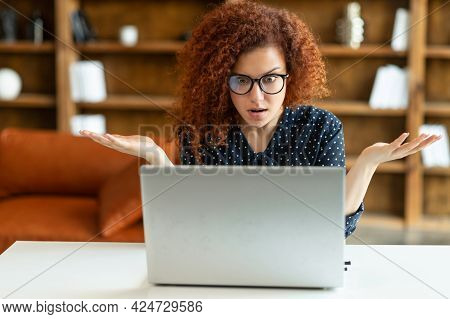 Puzzled And Confused Redhead Female Entrepreneur Staring At The Laptop Screen, Curly Woman In Shirt