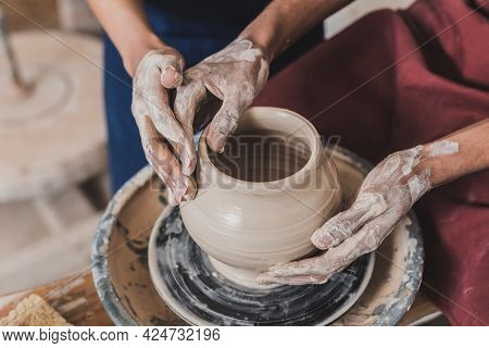 Partial View Of Young African American Couple Modeling Wet Clay Pot On Wheel With Hands In Pottery