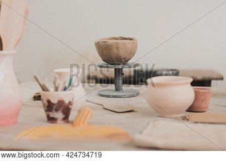 Sculpted Clay Bowl On Wooden Table In Pottery Art Studio