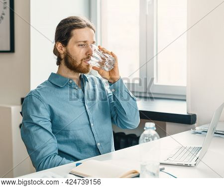 Young Male Freelancer Drinking Pure Mineral Water While Working On Laptop Remotely From Home, Male O
