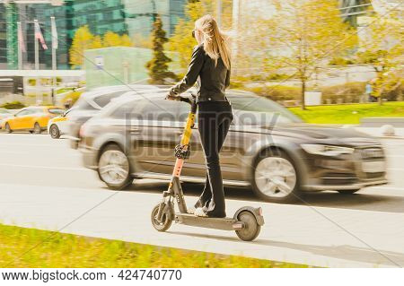 Moscow, Russia - May, 2021: Girl Rides A Kick Scooter Around The City Along The Road. Rear View Of W