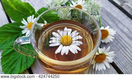 Chamomile Tea In A Glass Cup. Floral Background. A Bouquet Of Wildflowers And Raspberry Leaves In Th