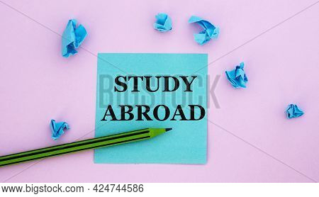 Study Abroad - Word On A Note Piece Of Paper On A Pink Background With Scattered Blue Crumpled Piece