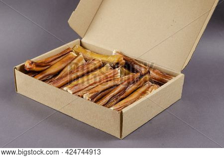 Pet Treats. Cardboard Box Full Of Chew Sticks. Natural Chewy Treats For Dogs On Gray Background. 6-i