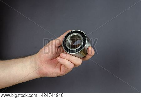 A Man Demonstrates Hub Bearing Against A Gray Background. New Metal Front Hub Bearing Of Passenger C