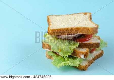 Ready-to-eat Food On A Light Blue Background. A Stack Of Appetizing Sandwiches With Chopped Ham, Tom