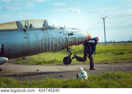 A Middle-aged Man Near An Old Abandoned Soviet Plane. Airplane On The Field Of The Old Airport.