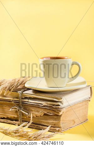 A Cup Of Coffee On Old Books And Dry Ears Of Corn In Yellow. Wellness, Harmony, Quiet Reading. Copy