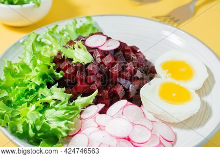 A Dietary Dish Made From Vegetables. Beet Tartare, Radish, Frieze Salad And Boiled Egg On A Plate On