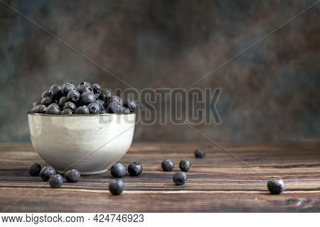 Blueberries In A Cup, On A Wooden Table. Blurred Background. Rustic Style. Healthy Diet. High Qualit