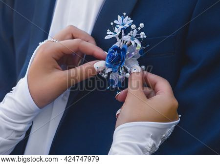 Hands Of The Bride In Wedding Gloves Touch The Decoration In The Form Of A Rose Flower On A Blue Sui