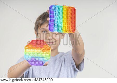 Boy Holding Sensory Pop It Fidget Toys In His Hands. Push Pop-it Fidgeting Game Helps Relieve Stress