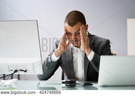 Upset Worried Man Using Laptop In Office
