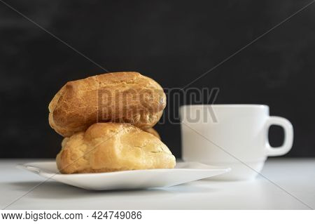 Fresh Eclairs Or Profiteroles And Cup Of Tea On Black Background. Home Tea Drinking.