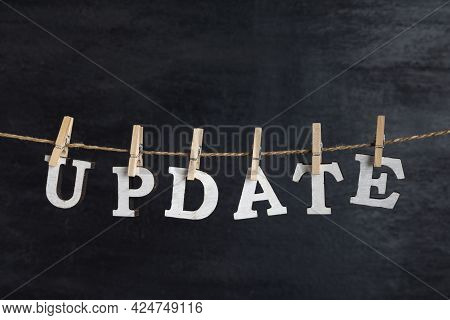 Word Update Held On Clothespin On Rope Against Black Background