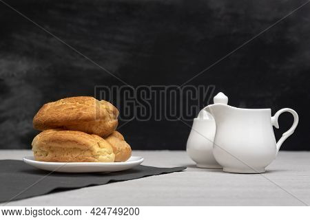 Homemade Eclairs And Creamer. Traditional French Eclairs. Gray Background.