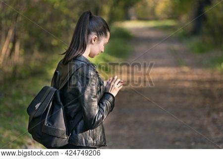 Young Girl Student Stands In The Park With Phone In Her Hands. Girl With Ponytail Is Walking In The