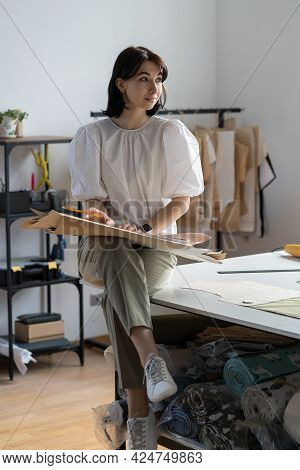 Trendy Fashion Designer Thinking On Patterns For New Clothes Sewing. Young Thoughtful Female Tailor