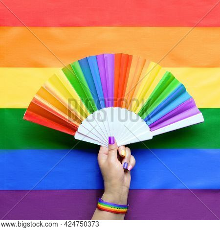 Hand With Hand Fan On Rainbow Lgbtqia Background, Top View. Simple, Minimal Lgbt Pride Decor For Jun