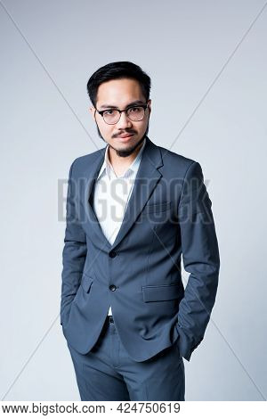 Handsome Korean Businessman In A Suit And Glasses With Hands In Pockets Stands On A Gray Background