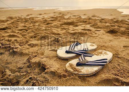 Flip-flops On A Sandy Beach Of Sea.