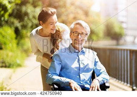 Senior Care And Wheelchair Transport. Smiling Woman Pushing Elderly Man