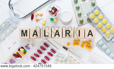 Malaria Word On Wooden Blocks On A Desk. Medical Concept With Pills, Vitamins, Stethoscope And Syrin