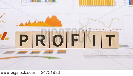 The Word Profit Made With Wooden Cubes On Table With Different Color Graphs And Diagram In Light Roo