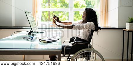 Disabled African Woman Stretching At Desk Working In Wheelchair