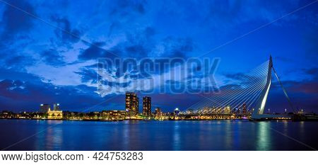 Panorama of Erasmus Bridge (Erasmusbrug) and Rotterdam skyline illuminated at night. Rotterdam, Netherlands