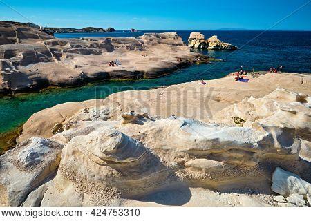 White rocks of famous tourist attraction of Milos island Sarakiniko beach with tourist relax and Aegean sea, Milos island , Greece