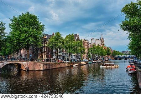 Amsterdam view - canal with tourist boat, bridge and old houses. Amsterdam, Netherlands