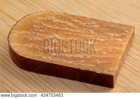Slice of old mature Dutch sheep milk cheese on a cutting board