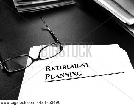 Retirement planning documents on desk with glasses for plan to retire
