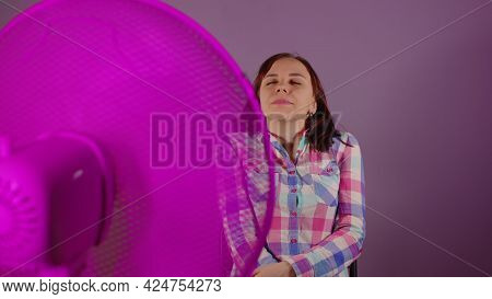 Close Up Of Young Woman Sitting On Chair In Front Of Fan On Purple Background. Happy Brunette With C