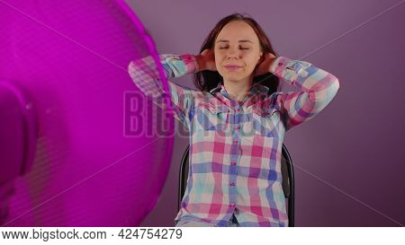 Close Up Of Young Woman Sitting On Chair In Front Of Fan On Purple Background. Happy Brunette Playin