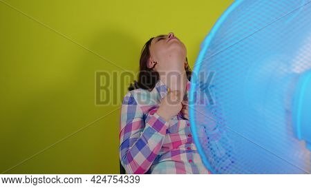 Close Up Of Young Woman Sitting On Chair In Front Of Fan On Yellow Background. Exhausted Brunette Es
