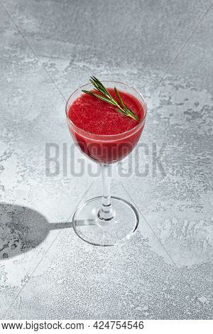 Red Square Cocktail is a classic cocktail with raspberry puree and vodka. Cocktail glass on vintage table with harsh shadow from sunlight. Red cocktail garnished with rosemary sprig