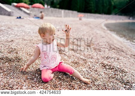 Little Girl Sits On A Pebble Beach Near The Water And Throws Pebbles Up