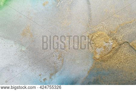 Art Abstract gold glitter and blue painting blots background. Alcohol ink colors. Marble texture.