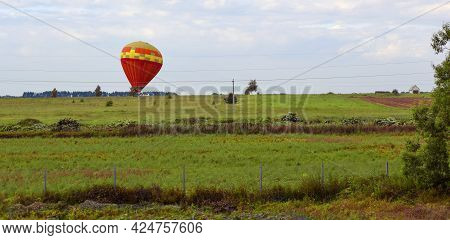 A Brightly Colored Hot Air Balloon Balloon Landed On A Large Green Field. Rural Landscape.