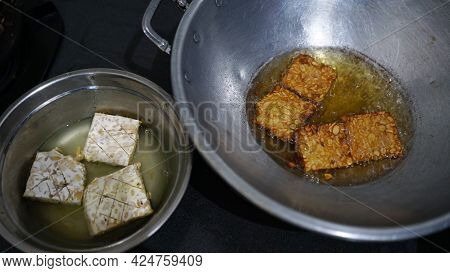 Tempeh Or Tempe That Is Being Fried In A Frying Pan And Tempeh That Has Not Been Fried. Focus Select