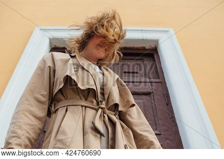 Young Millennial Woman With Wild Hair Dressed In An Autumn Coat Posing Near The Door Of An Old Build