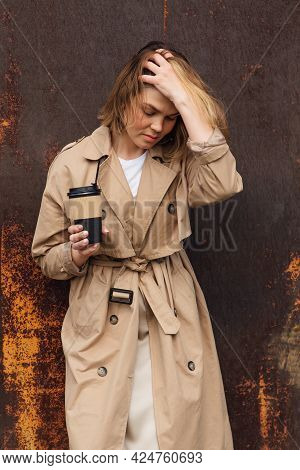 Young Millennial Woman With Wild Hair Dressed In An Autumn Coat Standing A Cup Of Coffee To Go Near