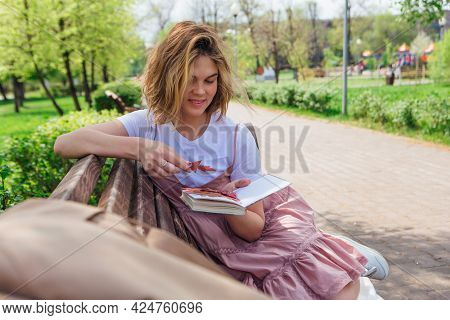Young Romantic Woman Sitting On Bench In Park And Reading Book