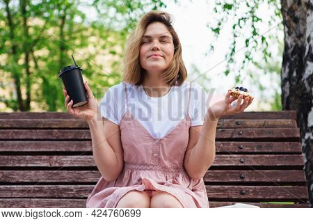 Young Romantic Woman Sitting On Bench In Park With Cake And Cup Of Coffee To Go