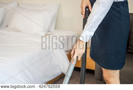 Room Service Maid Cleaning Hotel Room With Blurred Clean Fresh Towels On The Bed