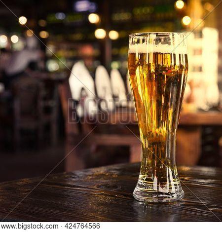 Glass Of Cold Lager Beer On Bar Or Pub Desk. Blurred Backgrounnd Of Bar Lights.